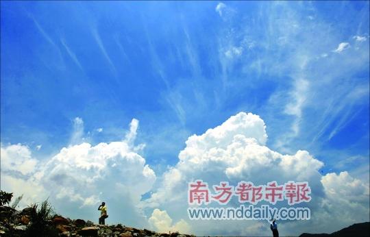 台风刚走,昨天惠州天气炎热,博罗洛阳镇2个男子走在东江大堤上.